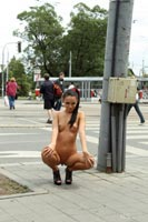 Undressed girl in high heels in the public street.